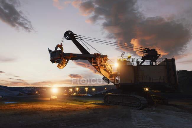 Silueta de una excavadora mecánica en una mina de mineral de hierro al atardecer, Tailandia - foto de stock