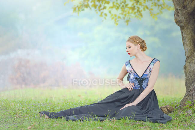 Ritratto di una bella donna seduta nel parco sotto un albero, Thailandia — Foto stock