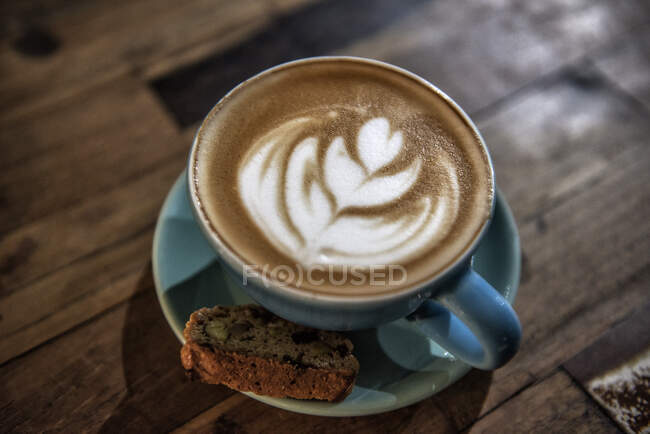 Cup of Piccolo latte with a Biscotti biscuit — Stock Photo