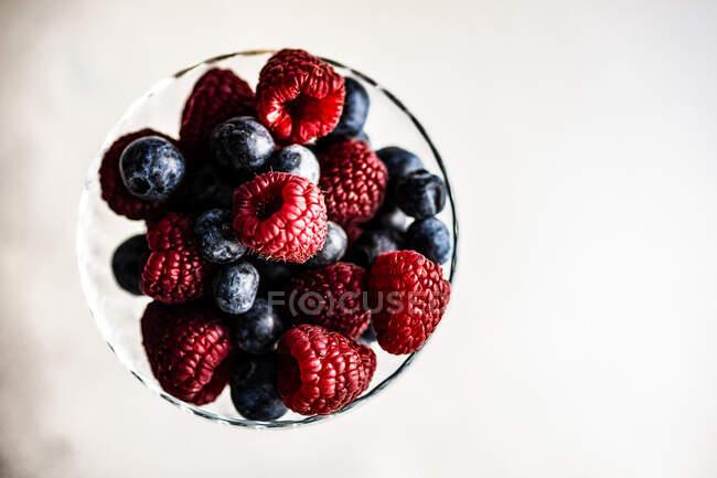 Стеклянная чаша со свежей малиной и черникой — Stock Photo