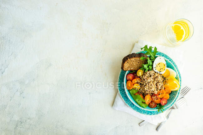 Healthy breakfast bowl with quinoa, chicken, vegetables and spices on the background of a table. top view — Stock Photo