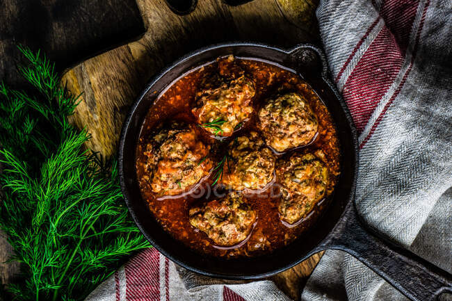 Baked potato with meat and spices in a cast iron skillet. selective focus. — Stock Photo