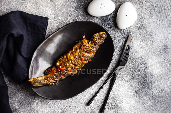 Grilled salmon with vegetables and spices on a black plate — Stock Photo