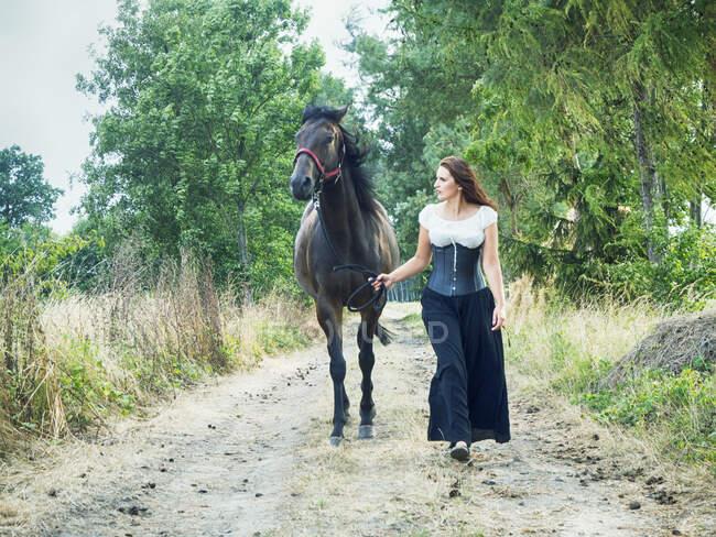 Красива жінка веде коня по сільській дорозі (Польща). — стокове фото