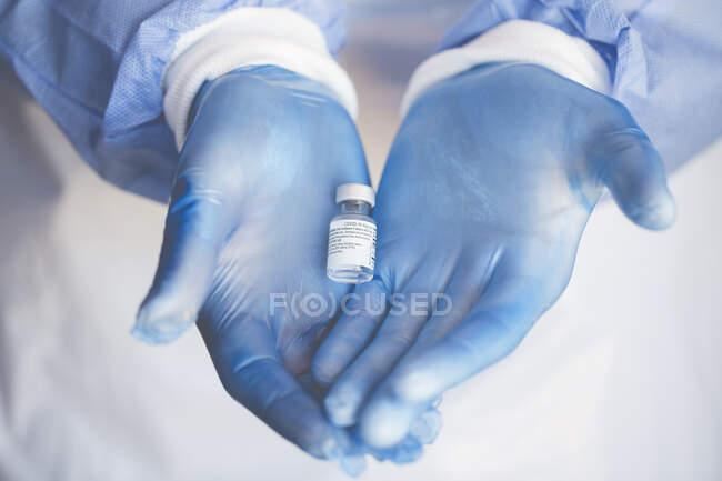 Enfermera que sostiene un vial de la vacuna contra el coronavirus - foto de stock