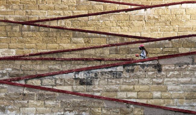 Mujer con máscara facial que baja por las escaleras del puerto, Cospisqua, Malta - foto de stock