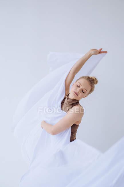 Frau tanzt mit weißem Stoff im Atelier — Stockfoto