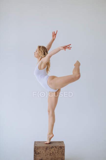 Turnerin im weißen Trikot steht auf einem Bein in einem Studio — Stockfoto