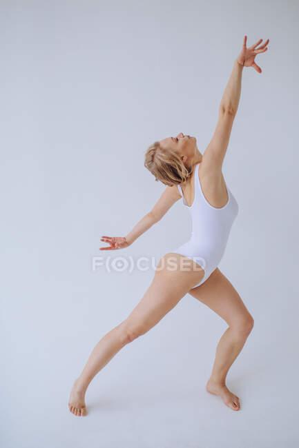 Turnerin im weißen Trikot tanzt in einem Studio — Stockfoto
