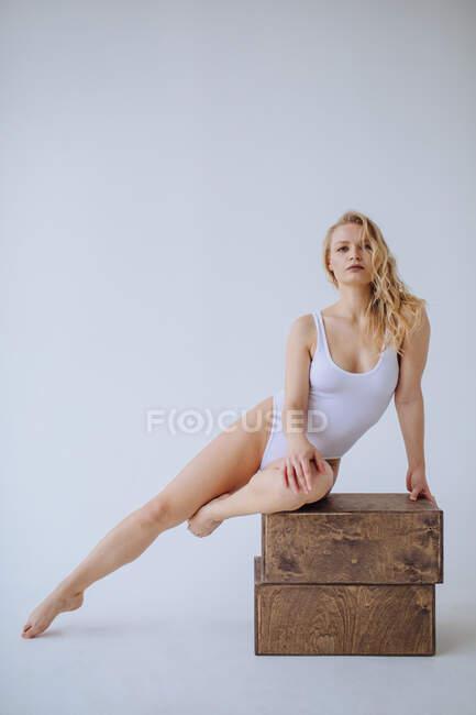 Turnerin im weißen Trikot sitzt auf zwei Holzklötzen — Stockfoto