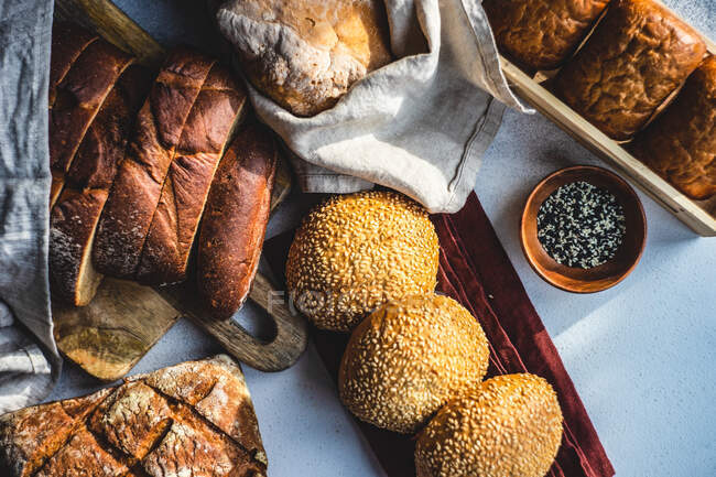 Overhead view of a variety of bread rolls and loaves of bread with sesame seeds — Stock Photo