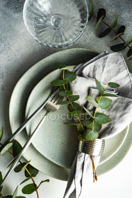 Ceramic plates place setting with eucalyptus stems — Stock Photo