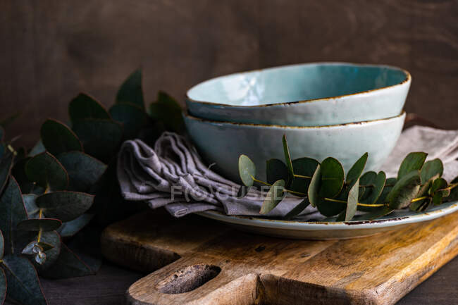 Stack of ceramic plates and bowls with eucalyptus stems — Stock Photo
