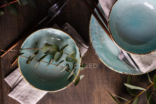 Place setting with eucalyptus stems — Stock Photo