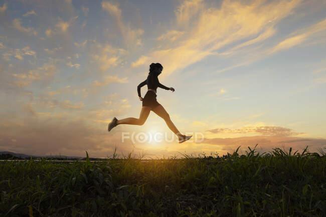 Seitenansicht einer Frau, die bei Sonnenuntergang läuft, Thailand — Stockfoto