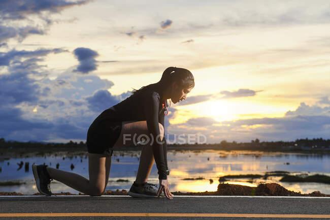 Frau macht sich bereit, entlang einer Uferstraße zu laufen, Thailand — Stockfoto
