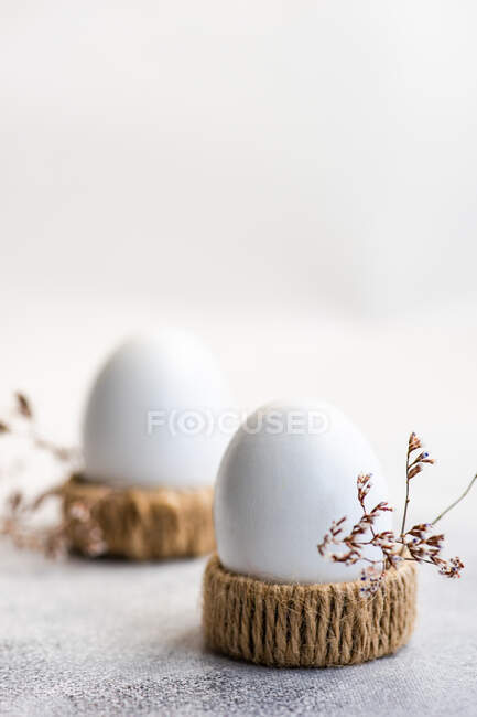Two boiled eggs in egg cups next to dried flowers — Stock Photo