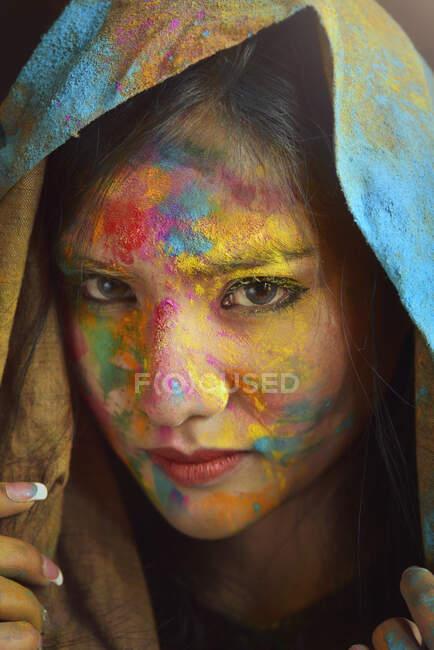 Ritratto di donna ricoperta di polvere multicolore durante la festa di Holi — Foto stock