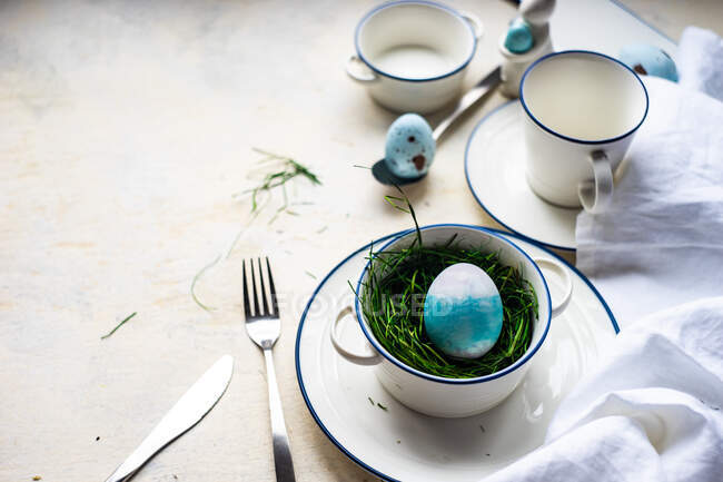 Easter place setting with an Easter egg, flowers and a feather — Stock Photo