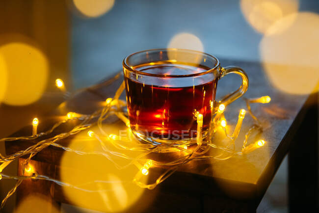 Taza de té rodeada de luces de hadas en una mesa - foto de stock