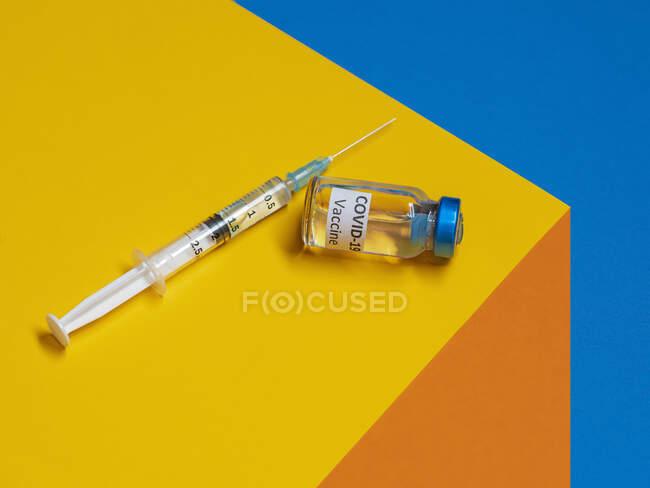 Vacuna y jeringa de Covid-19 sobre una mesa - foto de stock