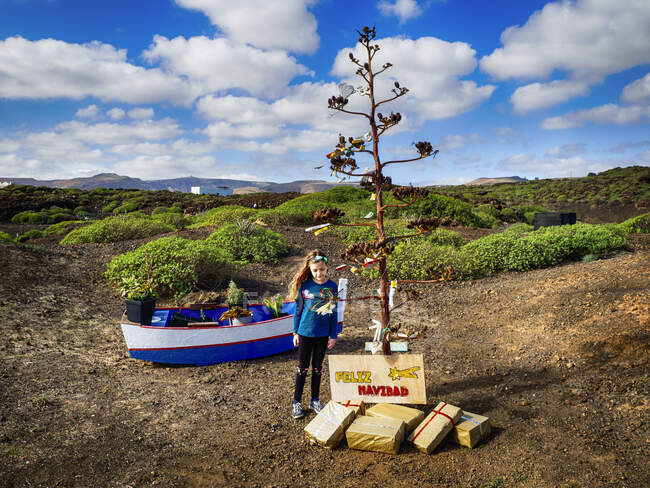 Girl standing next to a tree decorated with Christmas decorations in countryside, Lanzarote, Canary Islands, Spain — Fotografia de Stock