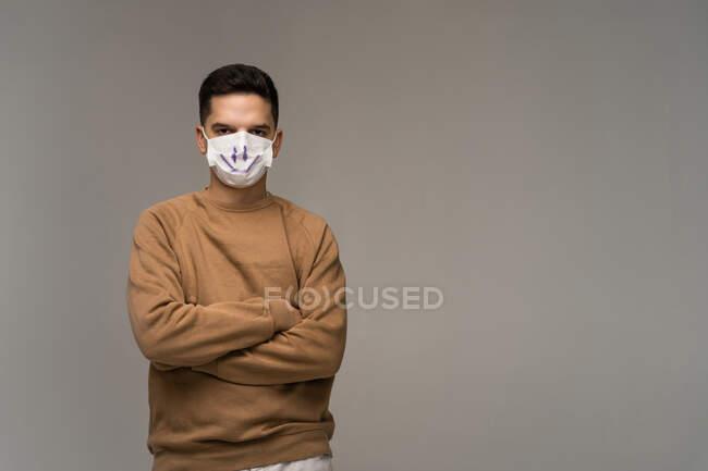 Ritratto di un uomo con le braccia incrociate che indossa una maschera con un volto sorridente — Foto stock