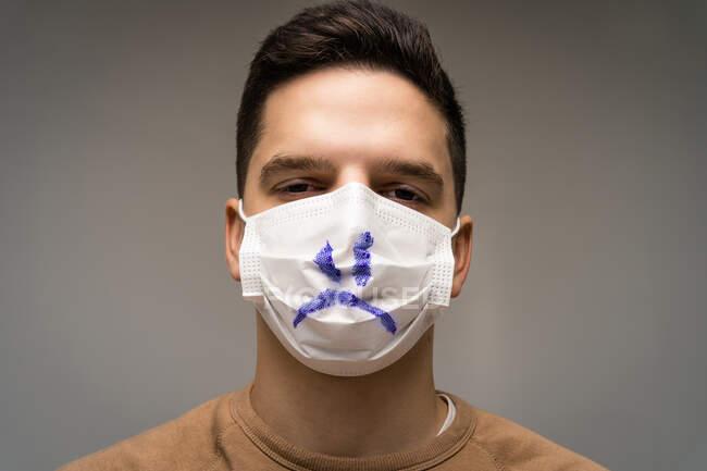 Ritratto di un uomo che indossa una maschera con un volto triste — Foto stock