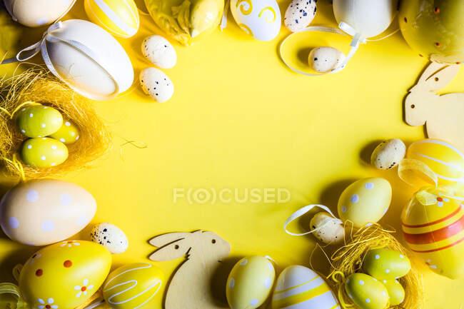 Decoraciones de huevo de Pascua y conejito de Pascua dispuestas sobre un fondo amarillo - foto de stock
