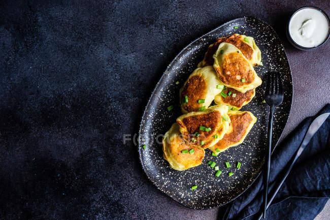 Ukrainian vareniki potato dumplings with chive garnish and sour cream — Stock Photo