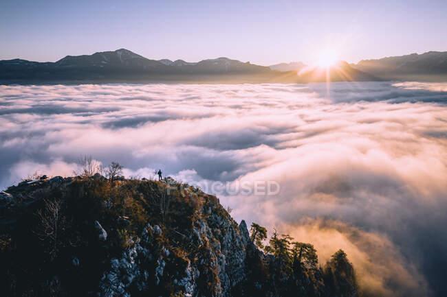 Man standing on mountain ridge rising above the cloud carpet, Hallein, Salzburg, Austria — Stock Photo