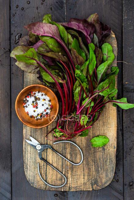 Свежие органические свекловичные листья на деревянном столе в качестве здоровой концепции приготовления пищи — стоковое фото