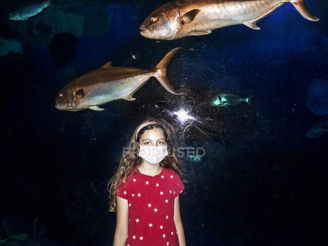 Mädchen mit Gesichtsmaske vor einem Aquarium in Italien — Stockfoto