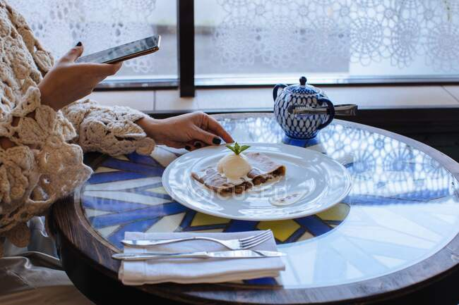 Woman sitting in a cafe taking a photo of strudel with ice-cream — Stock Photo