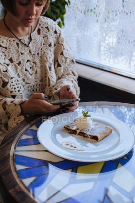 Femme assise dans un café prenant une photo de strudel avec de la glace — Photo de stock