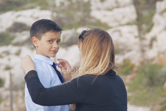 Retrato de uma mãe ajustando a gravata de seu filho — Fotografia de Stock