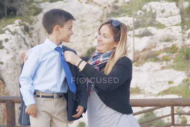Mãe de pé ao ar livre ajudando seu filho a se vestir — Fotografia de Stock
