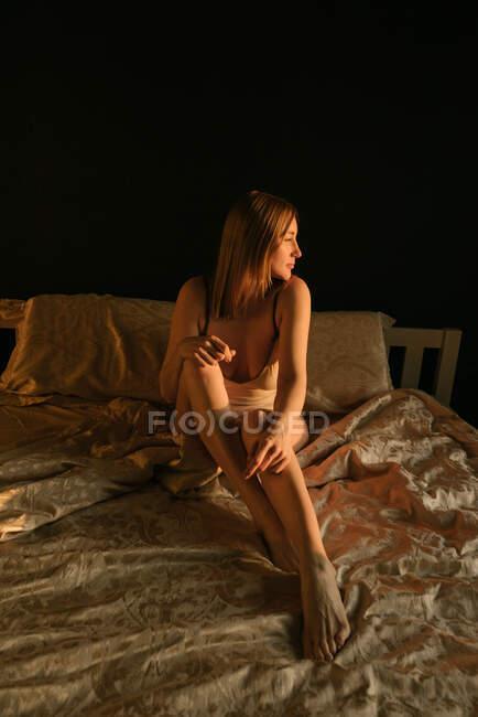 Frau in Dessous sitzt auf einem Bett und schaut zur Seite — Stockfoto