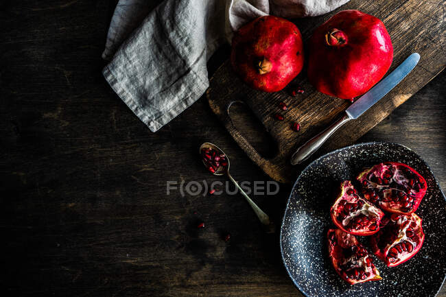 Organic pomegranate fruits with its seeds on plate as a organic food concept — Stock Photo