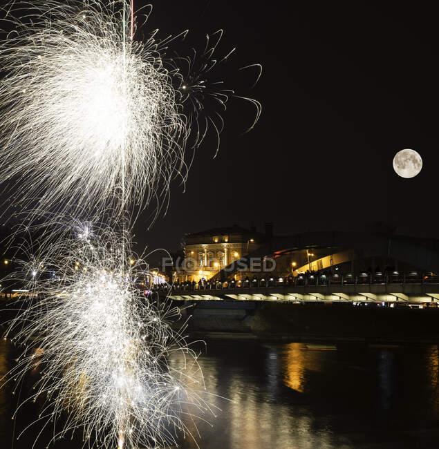 Fuegos artificiales sobre la ciudad por la noche, Vilnius, Lituania - foto de stock