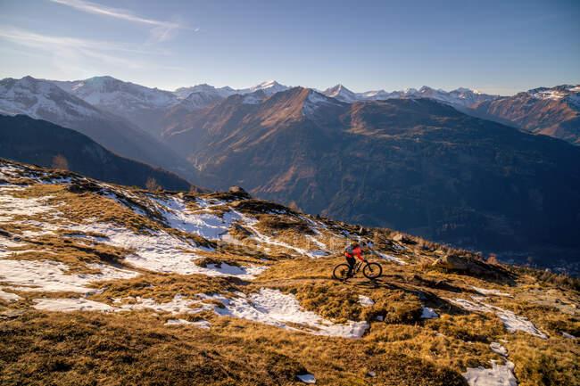 Mountainbikerin in alpiner Landschaft im Spätherbstschnee, Gastein, Salzburg, Österreich — Stockfoto