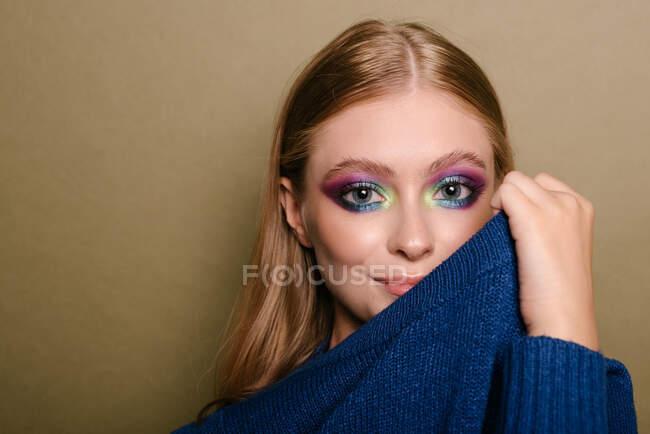 Ritratto di una bella donna con un trucco occhi che colpisce tirando il maglione sul suo viso — Foto stock