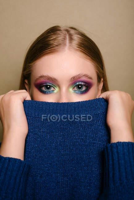 Retrato de una hermosa mujer con llamativo maquillaje de ojos sosteniendo un suéter sobre parte de su rostro - foto de stock