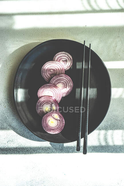 Red onion rings on black plate and chopsticks on stone background — Stock Photo