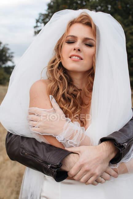 Mann hinter einer Braut mit den Armen um sie herum, Russland — Stockfoto