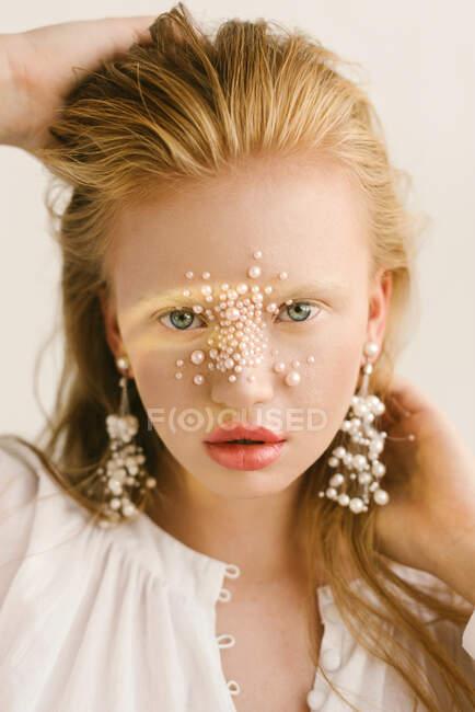 Retrato de una hermosa chica con perlas en la cara - foto de stock