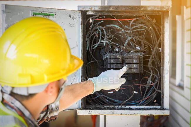 Электрик проверяет панель управления после пожара, Таиланд — стоковое фото
