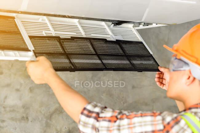 Técnico instalando una unidad de aire acondicionado en una pared, Tailandia — Stock Photo