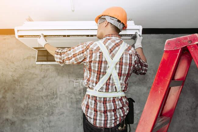 Técnico instalando una unidad de aire acondicionado en una pared, Tailandia - foto de stock