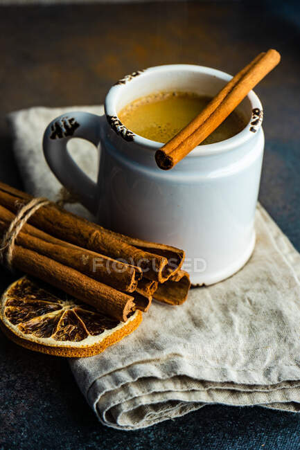 Mug of hot chocolate with cinnamon sticks and orange on rustic background with copy space — Stock Photo